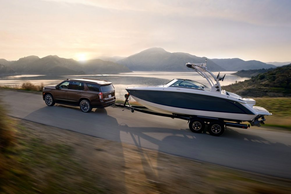 side view of a 2022 Chevrolet Tahoe RST towing a boat