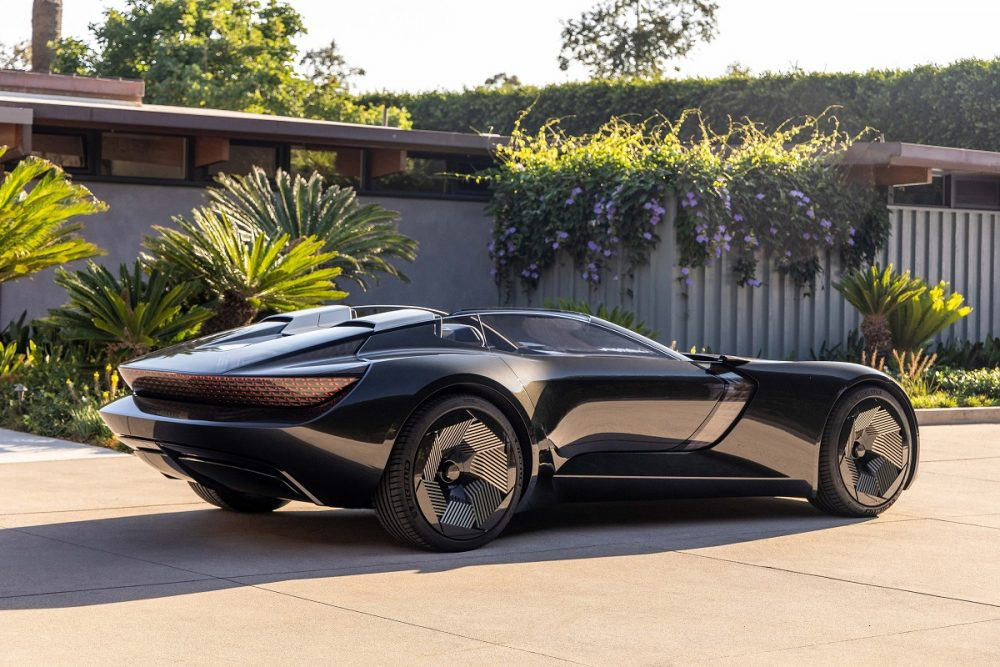 Rear side view of a black Audi skysphere concept parked at sunset in a residential area
