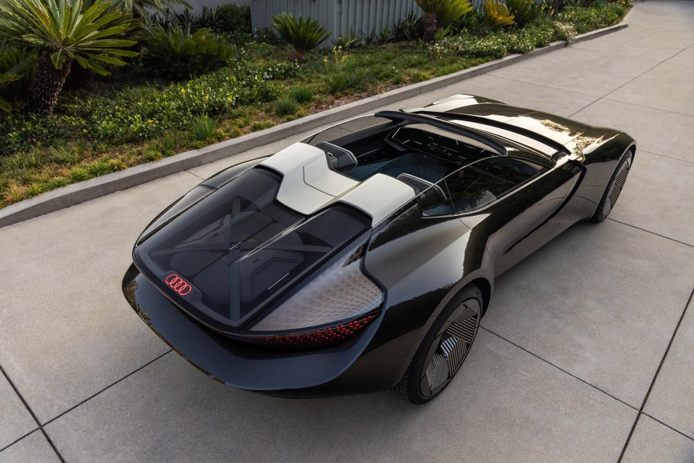 Rear aerial view of a black Audi skysphere concept parked at sunset in a residential area