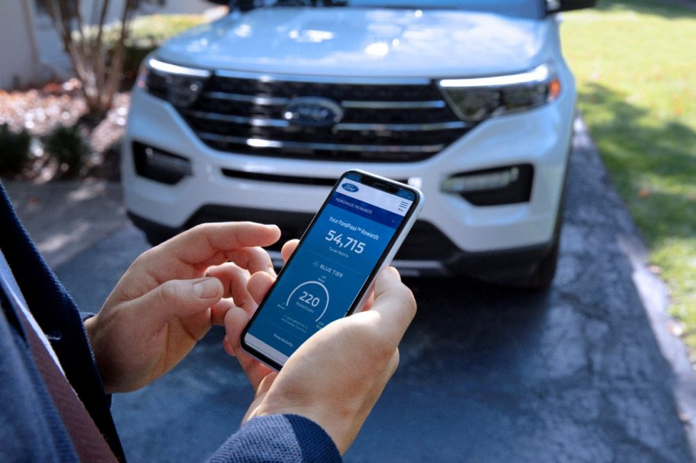 A FordPass Rewards user checking points in front of a Ford Explorer