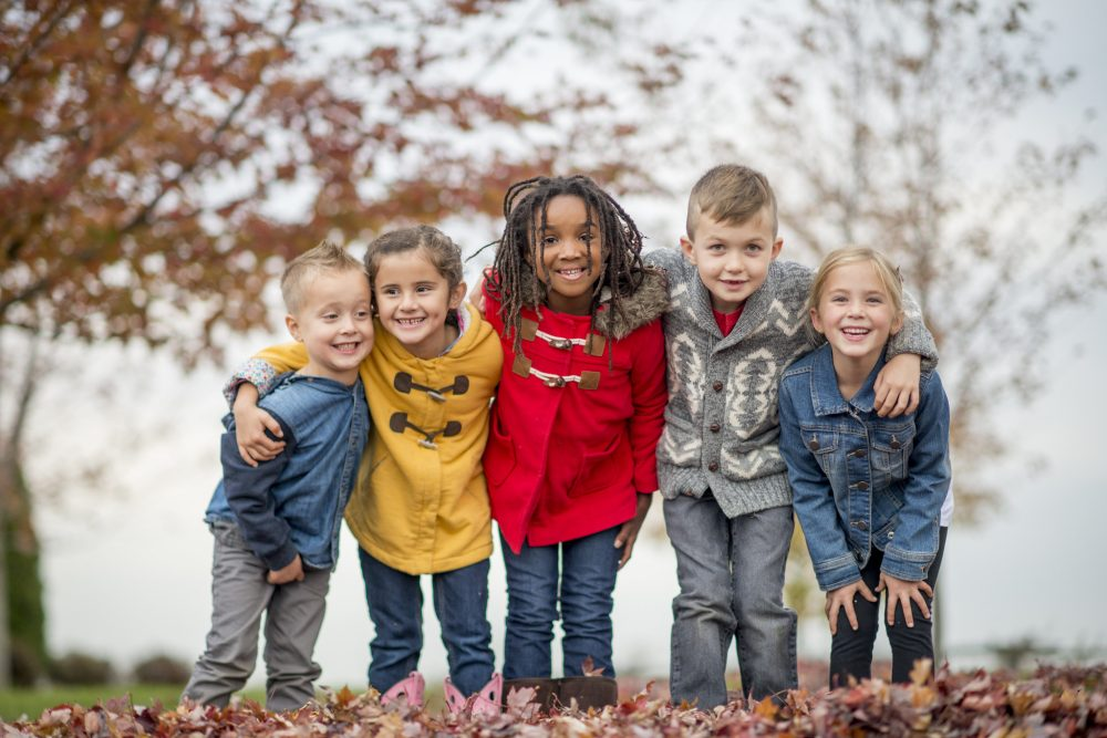 group of five children wearing coats and standing on a pile of autumn leaves with a tree in the background