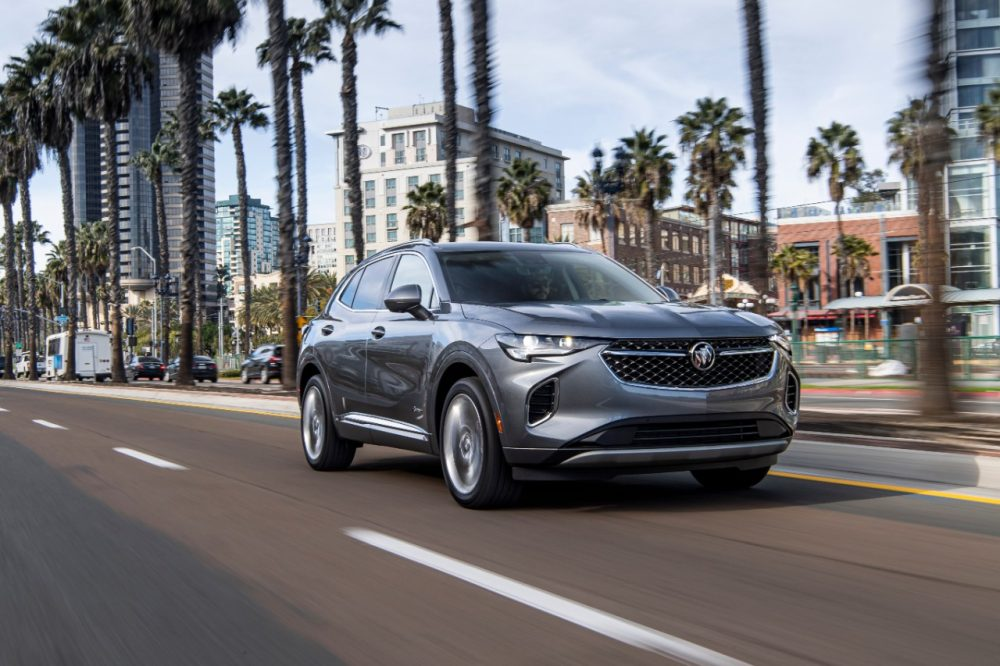 2022 Buick Envision driving down street with palm trees