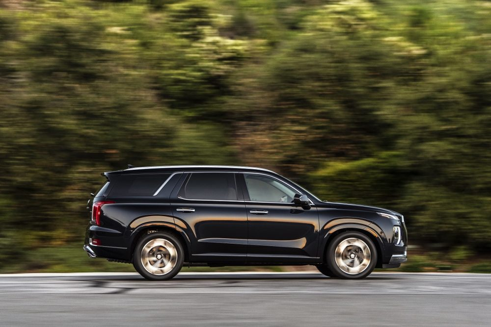 Side view of black 2022 Hyundai Palisade driving down road with trees in background