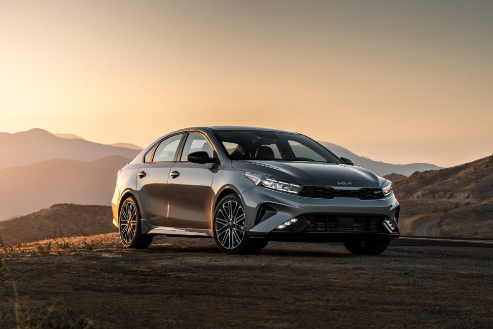 Front exterior view of a gray or silver 2022 Kia Forte parked on dirt at sunset