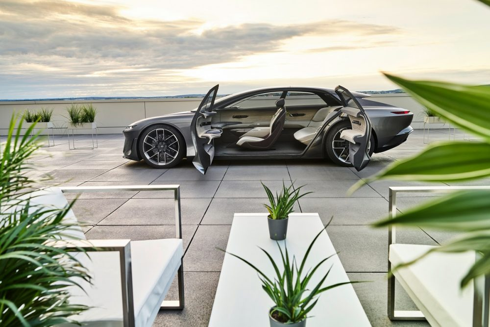 Side view of the Audi grandsphere concept with its doors open, parked at sunset
